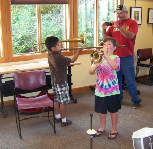 Two boys try out the brass.